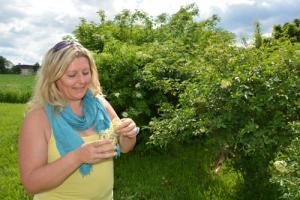 Eunike Grahofer gibt Holunderblueten in ein Glas
